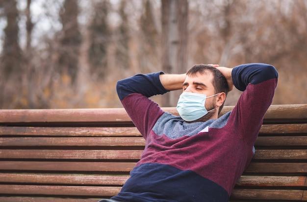 Facet z maską ochronną relaksujący, siedząc na ławce w parku o zachodzie słońca