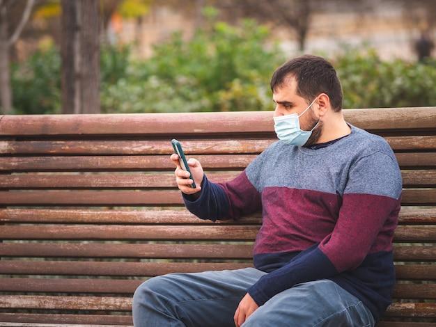 Facet z maską ochronną za pomocą smartfona na ławce w parku o zachodzie słońca