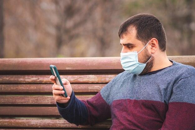 Facet z maską ochronną za pomocą swojego smartfona na ławce w parku o zachodzie słońca