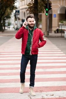 Facet z pełnym strzałem ze słuchawkami przechodzącymi przez ulicę