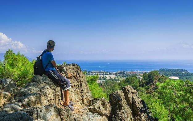 Facet z plecakiem na szczycie góry olympos patrzy na miasto kemer w turcji.