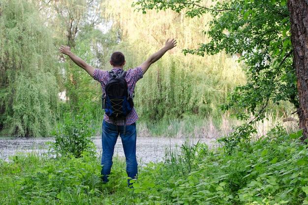 Facet z plecakiem stoi na brzegu leśnego jeziora z wyciągniętymi rękami,