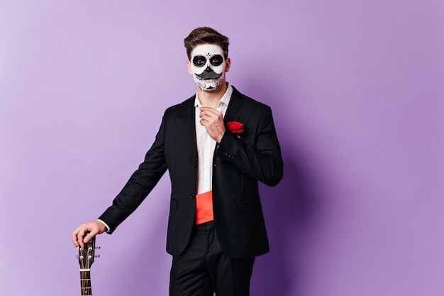 Facet z pomalowaną twarzą w klasycznym garniturze pozuje z fałszywymi wąsami, wsparty na gitarze.