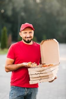 Facet z przodu dostawy trzyma kawałek pizzy