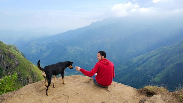 Facet z psem cieszący się górską scenerią na skraju urwiska