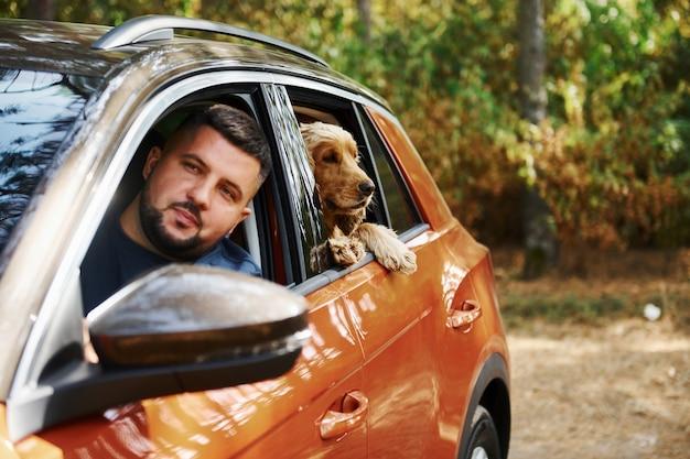 Facet z psem siedzi w nowoczesnym samochodzie w lesie i wygląda przez okno.