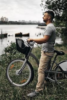 Facet z rowerem na brzegu rzeki w parku miejskim