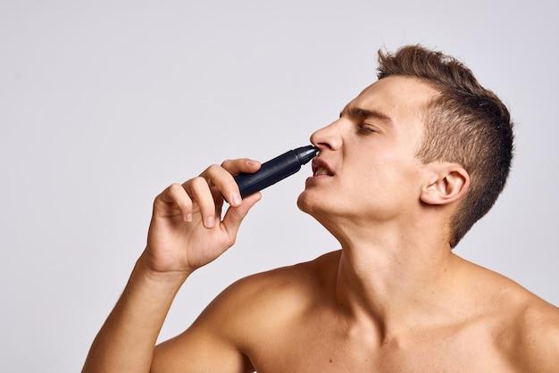 Facet z trymerem w ręku usuwa włosy z nosa nagich ramion