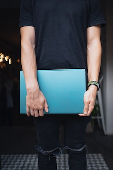 Facet z zamkniętym laptopem w dłoni, w pomieszczeniu