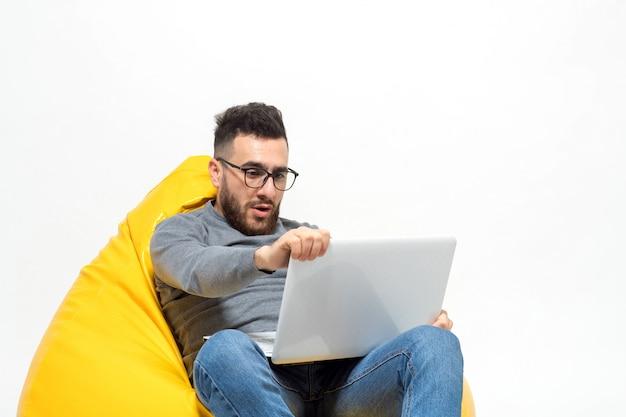 Facet zaskoczył siedząc na żółtym pufowym krześle