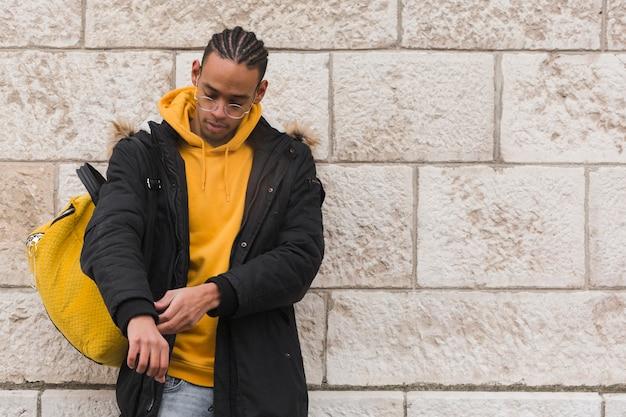 Facet ze średnim strzałem, żółty plecak i bluza z kapturem
