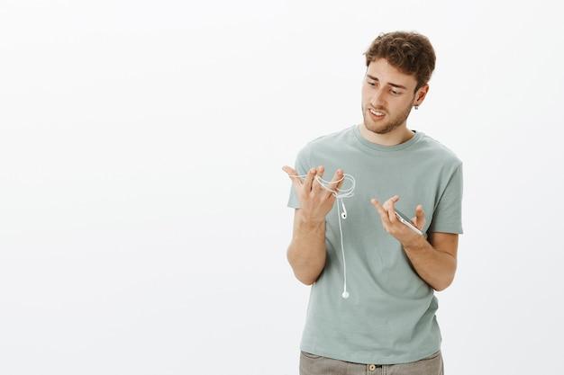 Facet znudzony przewodowymi słuchawkami, który chce kupić nowe bezprzewodowe słuchawki. ponury, skupiony młody mężczyzna o jasnych włosach, trzymający smartfon i słuchawki, próbujący rozwiązać przewody