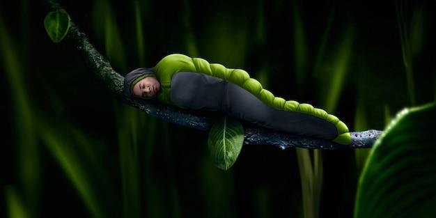Facet zorganizował biwak na gałęzi drzewa w zielonym śpiworze na łonie natury, otoczony zieloną trawą.