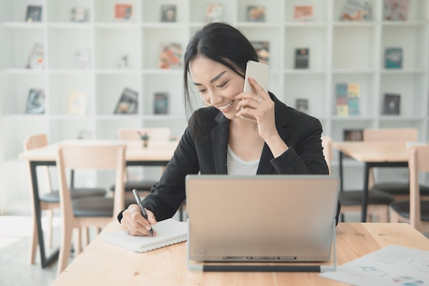 Fachowa kobieta pracująca opowiada z telefonem komórkowym i writng dokumentem dla wymieniać dane dane. praca w biurze z koncepcją technologii.