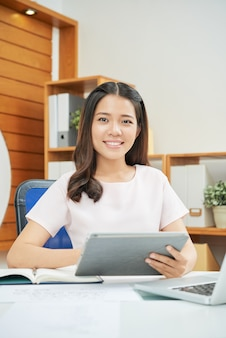 Fachowa uśmiechnięta kobieta z pastylką przy biurkiem