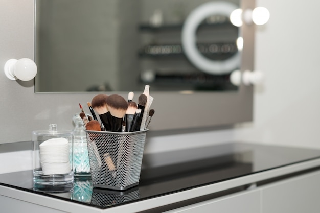 Fachowi makeup muśnięcia ustawiają zbliżenie blisko salonu lustra. pędzel dowolnego rozmiaru dla profesjonalnego makijażu na rozmycie tła