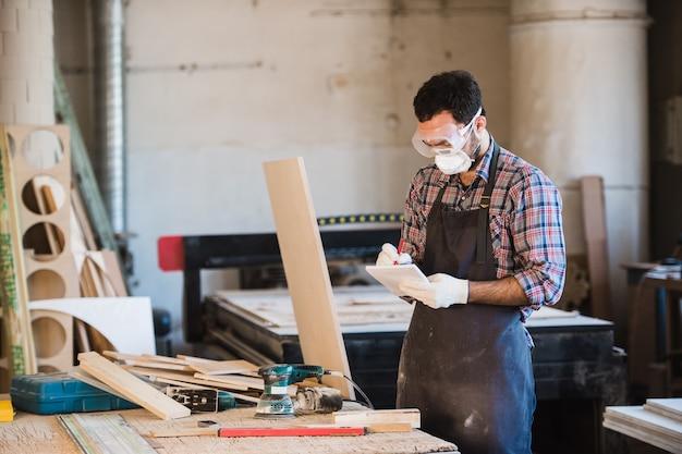 Fachowo ubrany stolarz lakierujący deskę