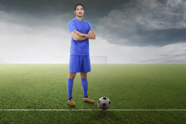 Fachowy azjatykci gracz futbolu z piłką przygotowywającą dla sztuki dopasowanie