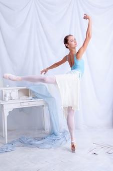 Fachowy baletniczy tancerz pozuje na bielu