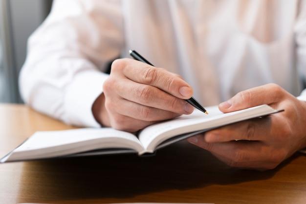 Fachowy biznesowego mężczyzna writing w notatniku