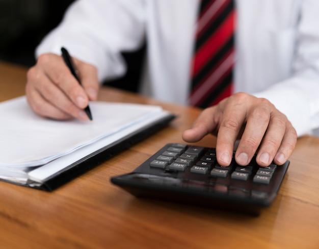 Fachowy mężczyzna pisać na maszynie liczby na kalkulatorze