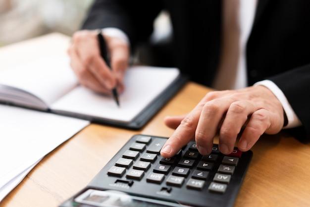 Fachowy mężczyzna pisać na maszynie na kalkulatorze