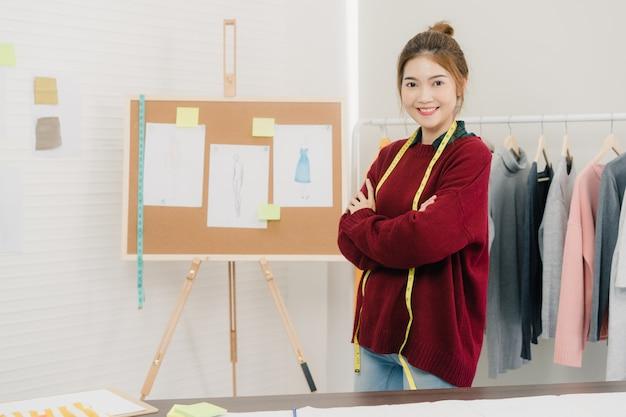 Fachowy piękny azjatycki żeński projektant mody pracuje pomiarową suknię na mannequin odzieży