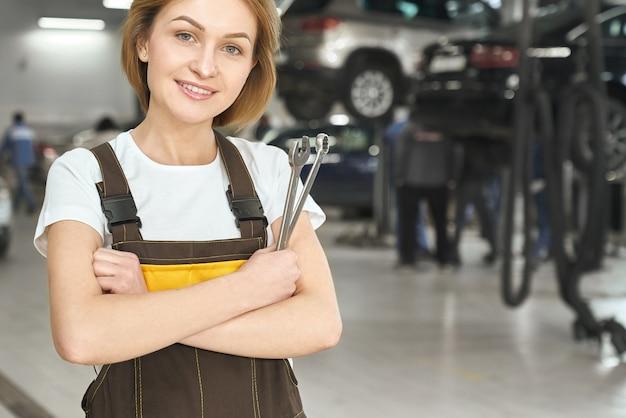 Fachowy żeński mechanik utrzymuje wyrwanie i pozować