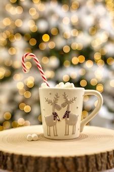 Fairy lights tła, gorące kakao z piankami, biały kubek z jelenia na drewnianym cięcie w domu podczas świąt bożego narodzenia i nowego roku. rozmycie bokeh.