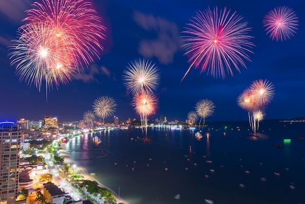 Fajerwerki nad morzem i widokiem na miasto w noc obchodów nowego roku.