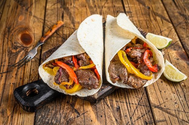 Fajitas tortilla wrap z paskami mięsa wołowego, kolorową papryką i cebulą oraz salsą. drewniane tło. widok z góry.