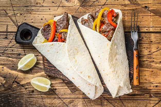 Fajitas tortilla wrap z paskami mięsa wołowego, kolorową papryką i cebulą oraz salsą. drewniany stół. widok z góry.