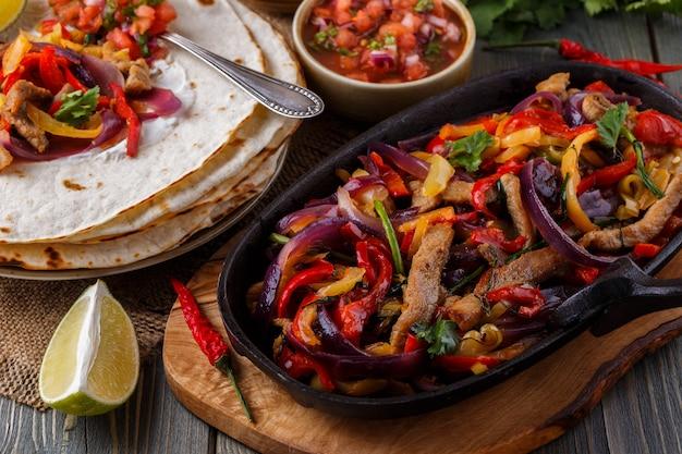 Fajitas wieprzowe z cebulą i kolorowym pieprzem, podawane z tortillami, salsą i śmietaną.