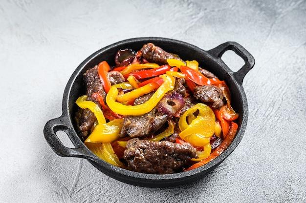 Fajitas wołowiny tradycyjne meksykańskie danie żywności na patelni. białe tło. widok z góry.