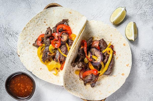 Fajity z paskami mięsa wołowego, kolorową papryką i cebulą, podawane z tortillami i salsą. widok z góry.