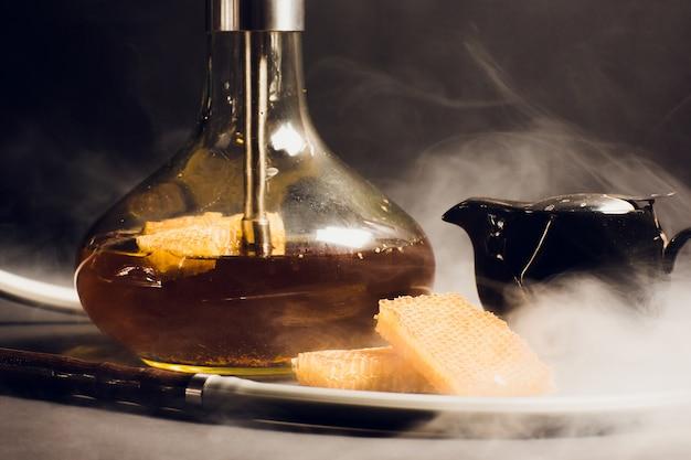Fajka wodna na bazie miodu, słodki smak fajki wodnej, obok plastrów miodu o strukturze plastra miodu