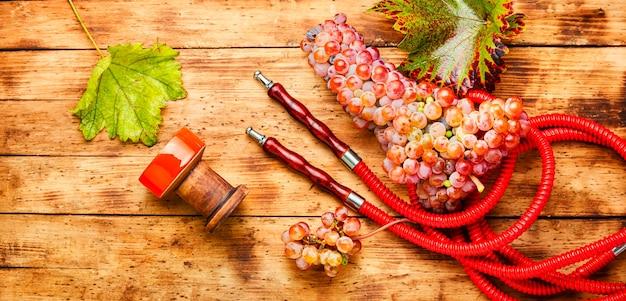 Fajka wodna z tytoniem winogronowym. pachnąca szisza winogronowa na drewnianym tle
