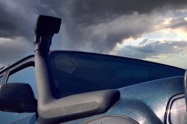Fajka zamontowana na suv-ie 4x4 na tle burzowego nieba. pojęcie podróży przygodowej.