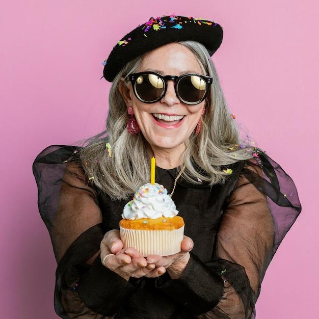 Fajna babcia świętująca urodziny babeczką