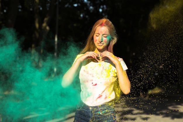 Fajna blondynka bawi się żółtą i zieloną suchą farbą holi w parku