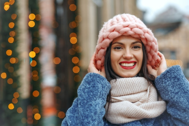 Fajna brunetka kobieta w płaszczu spaceru po mieście w zimie. pusta przestrzeń