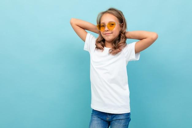 Fajna dziewczyna nastolatka w białej koszulce, żółte okulary uśmiecha się i pokazuje się na białym tle na niebieskim tle