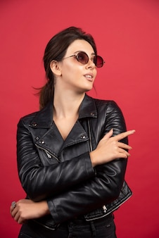 Fajna dziewczyna w czarnej skórzanej kurtce pozuje w czarnych okularach przeciwsłonecznych.