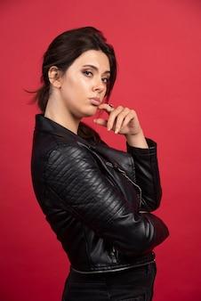 Fajna dziewczyna w czarnej skórzanej kurtce przykłada palec do brody i myśli.