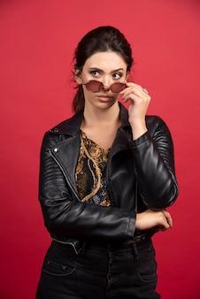 Fajna dziewczyna w czarnej skórzanej kurtce, wyjmując okulary przeciwsłoneczne i uśmiechając się.