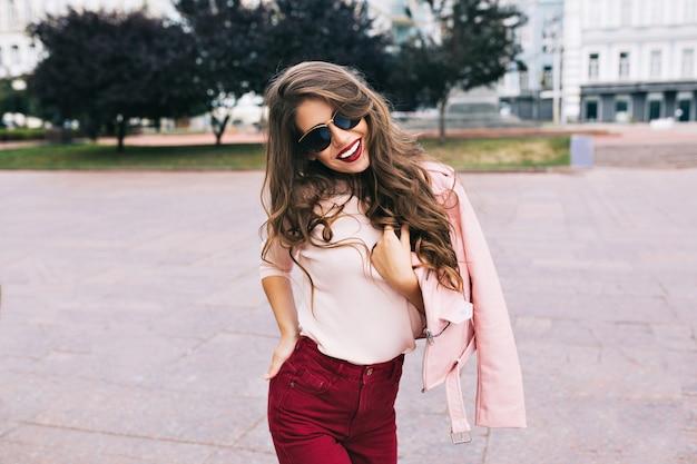 Fajna dziewczyna w spodniach marsala z długimi fryzurami pozuje w mieście. nosi okulary przeciwsłoneczne i się uśmiecha.