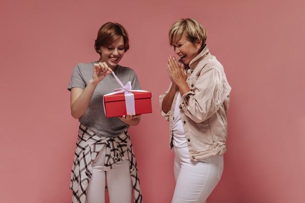 Fajna dziewczyna z krótką fryzurą w t-shirt, koszuli w kratę i lekkich spodniach, otwierająca czerwone pudełko i pozująca z wesołą staruszką na różowym tle.