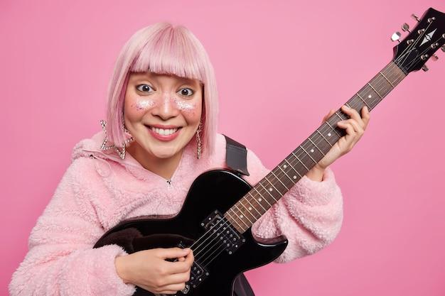 Fajna gwiazda rocka gra na gitarze akustycznej, uśmiecha się pozytywnie i ma różową fryzurę z instrumentem muzycznym