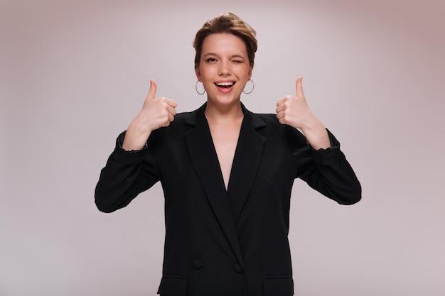 Fajna kobieta mrugająca i pokazująca duże kciuki. ładna dziewczyna w czarnej kurtce szeroko uśmiechając się i patrząc w kamerę na na białym tle