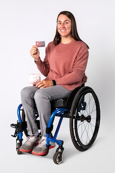 Fajna kobieta na wózku inwalidzkim pokazująca kartę kredytową premium